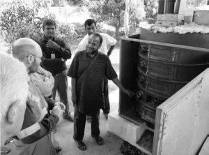Dr Ravi Kumar, inventor of the Anila cooking stove, standing beside the BiGchar-1000, a continuous-flow pyrolysis unit by Black-is-Green Pty Ltd Australia. Its inventor, Dr James Joyce, is on the left.